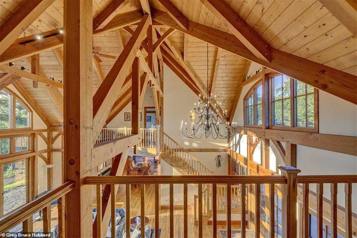 Depuis le porche couvert, la grande salle s'ouvre, avec un plancher de plafond, foyer en pierres, plafond cathédrale, et d'un lustre
