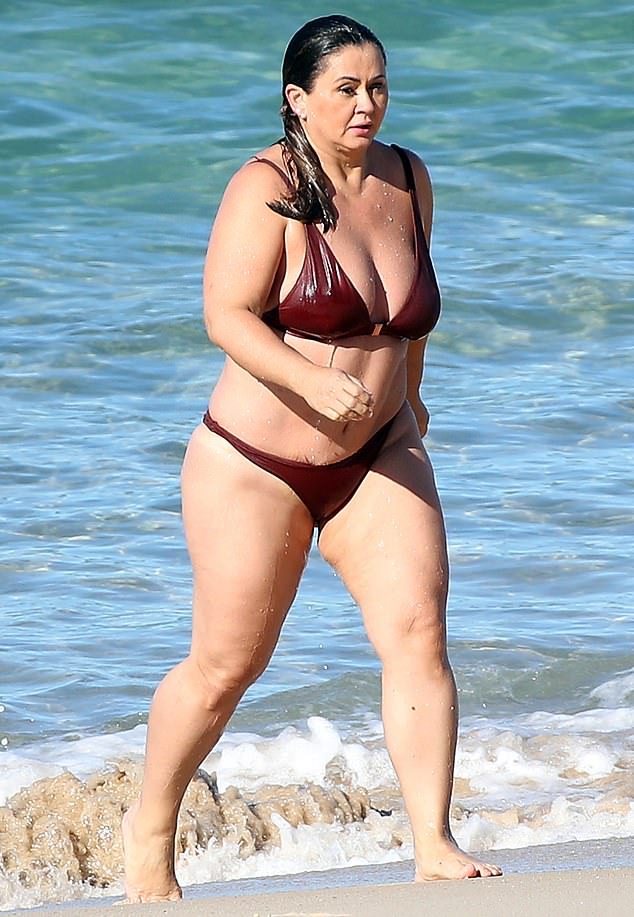 Bikini body: Channelling her inner Bond Girl, Mishel was seen striding in and out of the water in a barely-there maroon bikini set