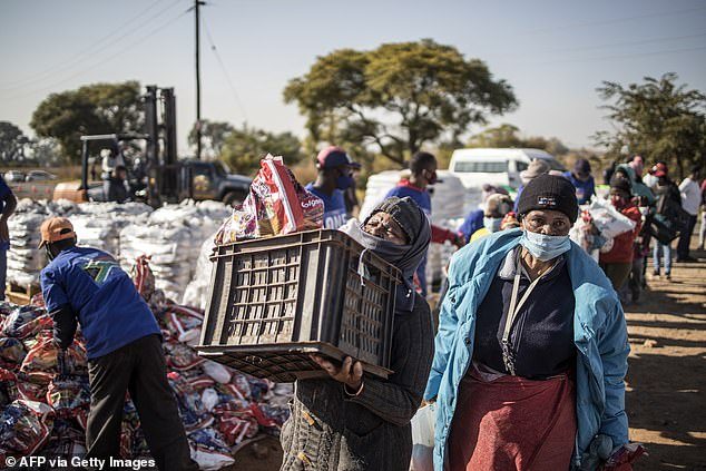 Pictured:A woman carries a food hamper, masks, soap and sanitiser during a distribution organised by different charities at the Iterileng informal settlement near Pretoria, South Africa