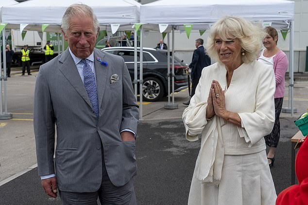 The Duchess of Cornwall uses her signature socially-distant greeting as she arrives alongside Prince Charles (pictured)