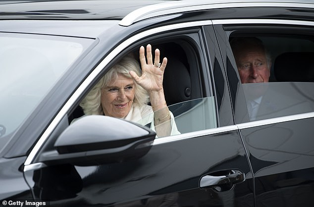 Camilla waves from the front seat of a car following a visit with Prince Charles to the shirt factory