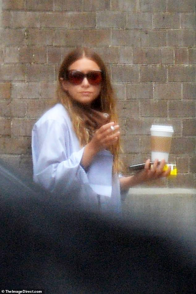 Taking in the big city: Ashley pulled down her bandanna to enjoy a cigarette with her coffee