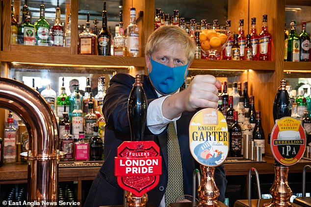 Boris Johnson wears a mask as he pours a pint at the Crown and Treaty pub in Uxbridge this evening