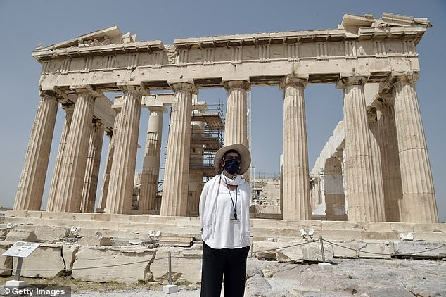 The news comes shortly after British tourists were advised to wear face masks at all times while abroad by a group of the world's leading travel agencies. Pictured: A woman wearing a face mask stands in front of the Acropolis in Athens