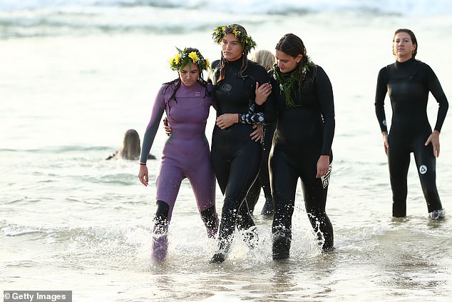 The group of mourners donned wreaths of flowers around their heads and surf swimsuits (pictured on Saturday morning, Ms Vlug in a headdress and black wetsuit)