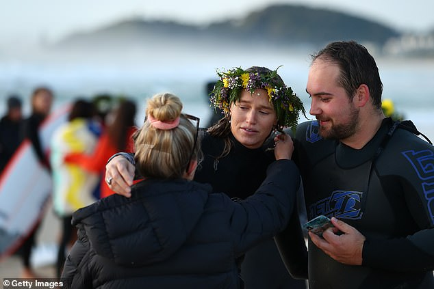 Family and friends comfort a tearful Ms Vlug (pictured) during the morning service on Saturday