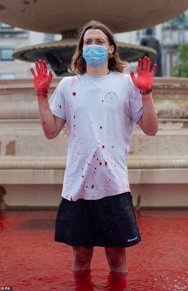 An Animal Rebellion protester stands in the fountains at Trafalgar Square in London this afternoon