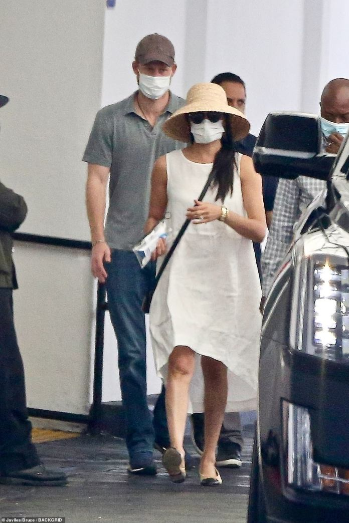 Meghan wore a loose cream linen dress with matching cream and black ballet flats, and accessorized her outfit with a large straw hat and dark sunglasses
