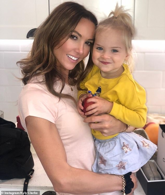 'My friends are my family': Kyly appeared to be in high spirits as she cuddled up to one of her friend Dominika's daughters for a happy snap