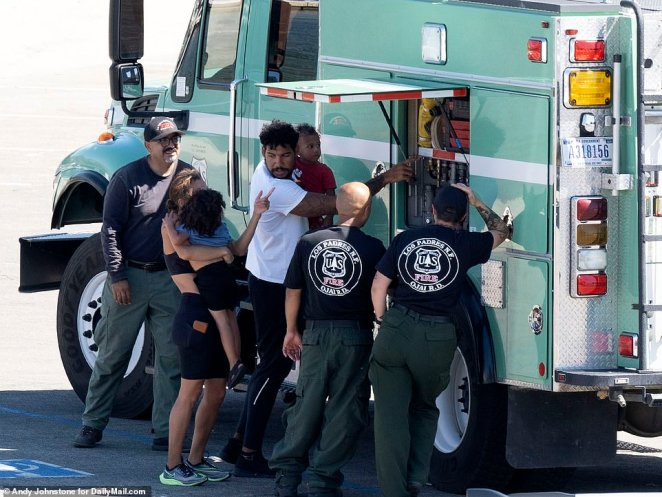 Naya Rivera's brother, seen in the white t-shirt, and their sons distracted themselves by looking at a nearby fire truck