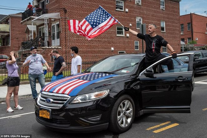 Another man waves the Stars and Stripes from the front seat of a carduring a Blue Lives Matter rally in Bay Ridge, Brooklyn, on Saturday