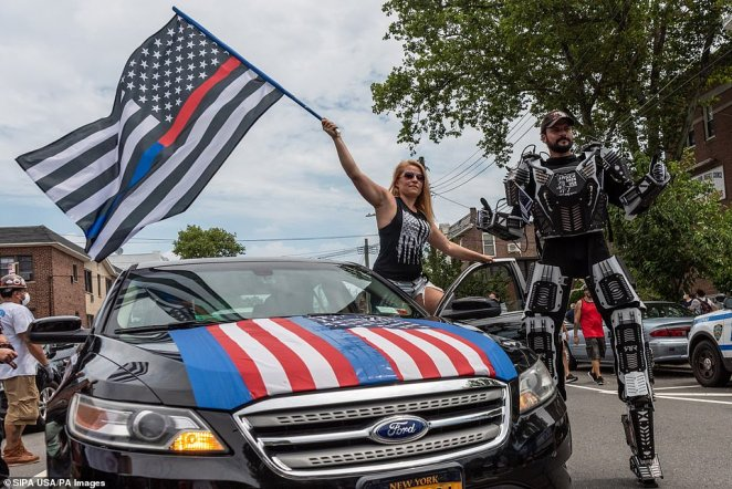 One woman waves a 'thin blue line' American flag from the front seat of her car while another is dressed in what appears to be a Transformers costumeduring a Blue Lives Matter rally in Bay Ridge, Brooklyn, on Saturday