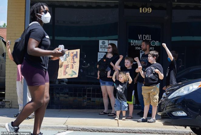 Onlookers raise a fist in solidarity as anti-racist protesters with the Burlington-Alamance March For Justice and Community march to the Confederate monument at the Alamance County courthouse in Graham