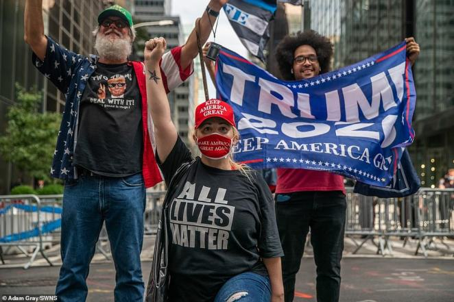 Trump supporters with shirts that say 'All Lives Matter' and waving banners that read 'Trump 2020' pose for photographsduring a demonstration in front of Trump Tower in New York City on Saturday