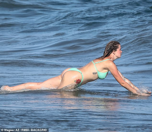 So much fun: She also took a dip in the water and at one point was spotted lying down on her front as the waves rose in front of her