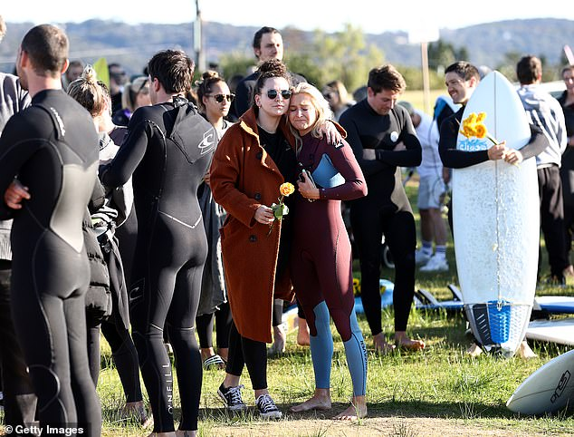 A friend of Pullin's is comforted as she cries at a moving tribute to the late snowboarder