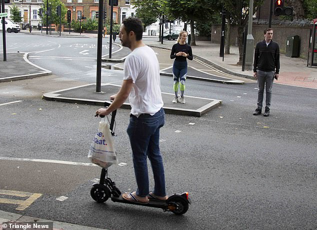 A man in a T-shirt and jeans rides an electric scooter in his flip-flops without wearing a helmet.  He is holding a Tesco carrying bag on the handlebars