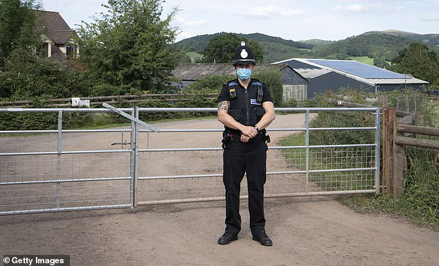 An officer wearing a face mask stands at the entrance to AS Green and Co Farm, where employees have tested positive for Covid-19