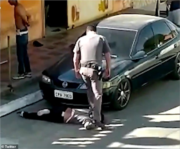 Two officers filmed violently arresting a group of people in Sao Paulo, Brazil, back in May will now face criminal charges - including cop who stood on a black woman's neck (pictured)