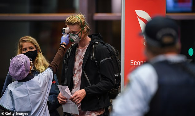 Travellers are temperature tested by health officials after arriving on a Qantas flight from Melbourne to Sydney on July 7