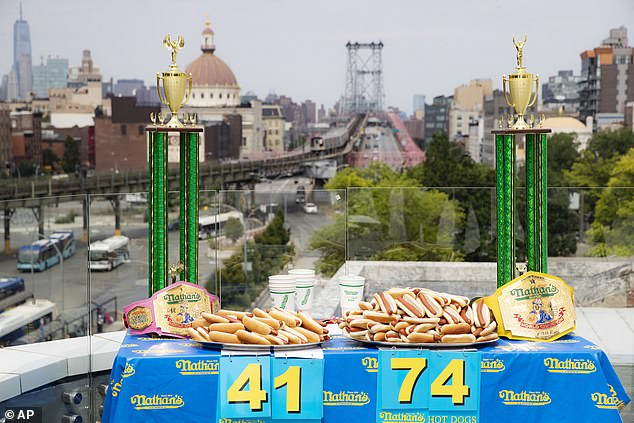 California's Joey Chestnut set his latest world record on July 4, 2020, which also saw him secure his 13th title at the Nathan's Hot Dog Eating Contest. The same event saw a new world record and the the seventh consecutive victory for America's Miki Sudo in the women's competition, in which she consumed 48.5 hot dogs in a span of ten minutes. Pictured, hot dogs and trophy belts lain out before the weigh in at the famous competitive eating event this year