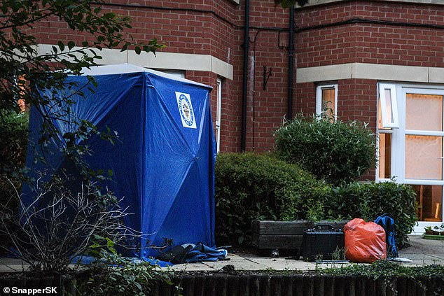 West Midlands Police guard a ground floor flat on Warwick Road in Solihull. A blue tent was placed to protect evidence at the scene