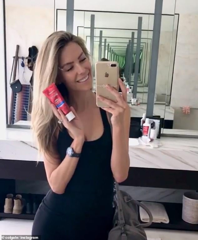 Jennifer Hawkins shows off her bottle of Colgate's  Optical White Renewal toothpaste