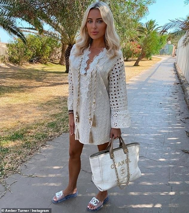Lovely: She shared another shot at the beach club, this time wearing a white English embroidery dress associated with Chanel accessories