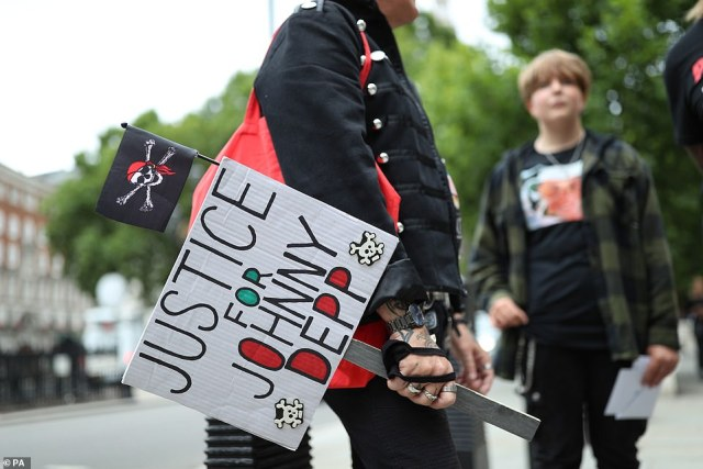 A man holding a placard in support of Depp stands outside the High Court in London this morning ahead of the latest hearing