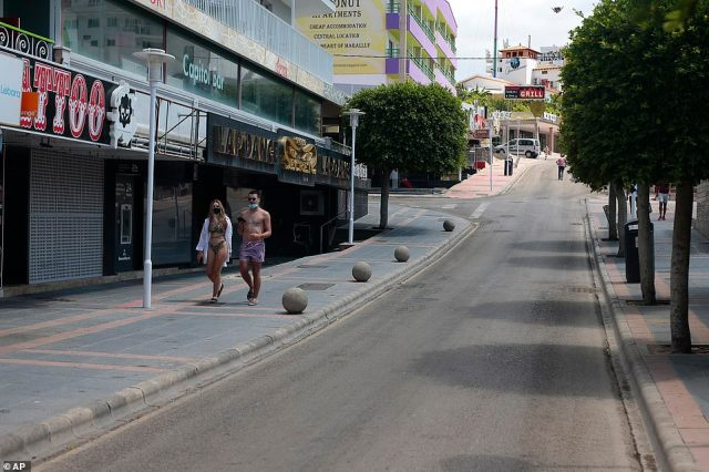 Tourists walk along an empty street at the resort of Magaluf