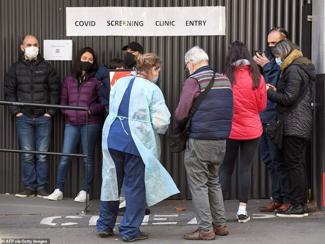 A medical worker (centre left) speaks to people queueing outside a COVID-19 coronavirus testing venue at The Royal Melbourne Hospital in Melbourne