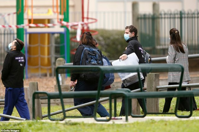 Government employees are seen entering the Alfred Street Public Housing Complex in North Melbourne