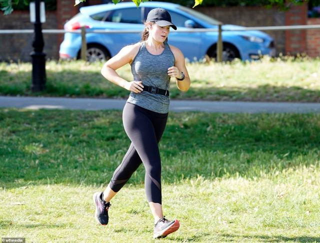 A woman is seen on a jog in the bright sunlight on Friday morning on Clapham Common