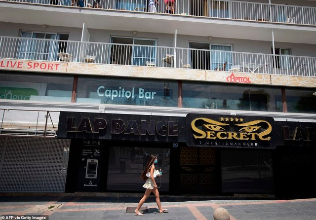 This woman was seen walking past another shuttered club on Magaluf's Punta Ballena strip on Thursday