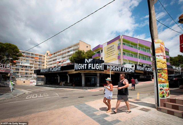 On Magaluf's famous Punta Ballena strip of bars and clubs, all of which were forced to close earlier this week, two tourists were seeen walking past deserted establishments