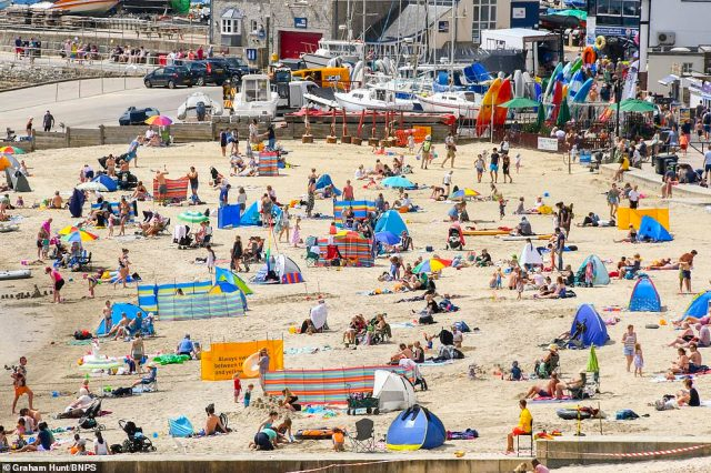 Sun-seekers flocking to the beach at the seaside resort of Lyme Regis in Dorset today on a day of scorching hot sunshine