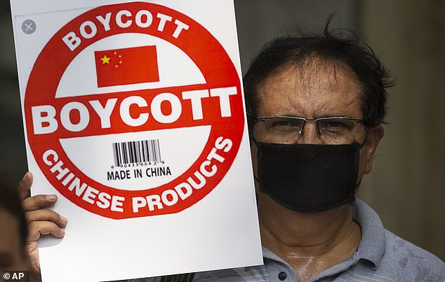 An Indian journalist holds a placard calling for boycott of Chinese products (pictured on June 30)