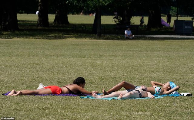 Three women chat and sunbathe on Clapham Common in south London today as temperatures soar to 84F
