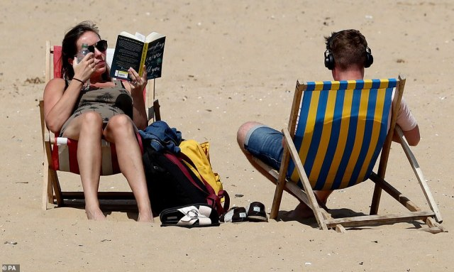 People enjoy the warm weather on the beach in Margate, Kent, as parts of the UK enjoy warm weather today