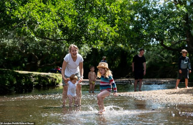 Pictured: Jola and her daughter Isla (one) and Rowan (three) enjoying the warm weather as they paddle in the Lymington River at Balmer Lawn in the New Forest, Hampshire today