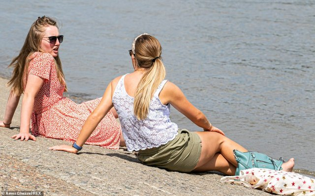 Two people enjoy the sizzling sun along the Putney embankment in London today as temperatures soar to 84F today