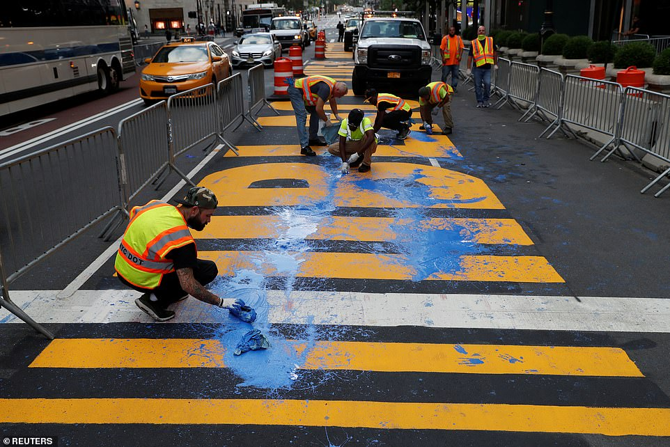 City workers are seen cleaning the blue paint off the mural after it was covered on Friday afternoon