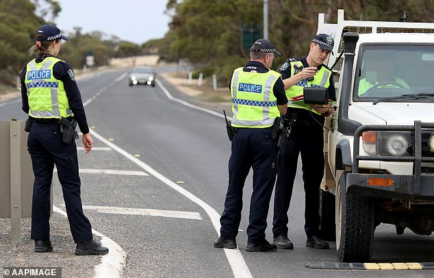The state reintroduced its hard border closure with Victoria on July 9, meaning only SA residents or those with special exemptions are allowed into the state (pictured: officers man the Pinaroo border in South Australia)