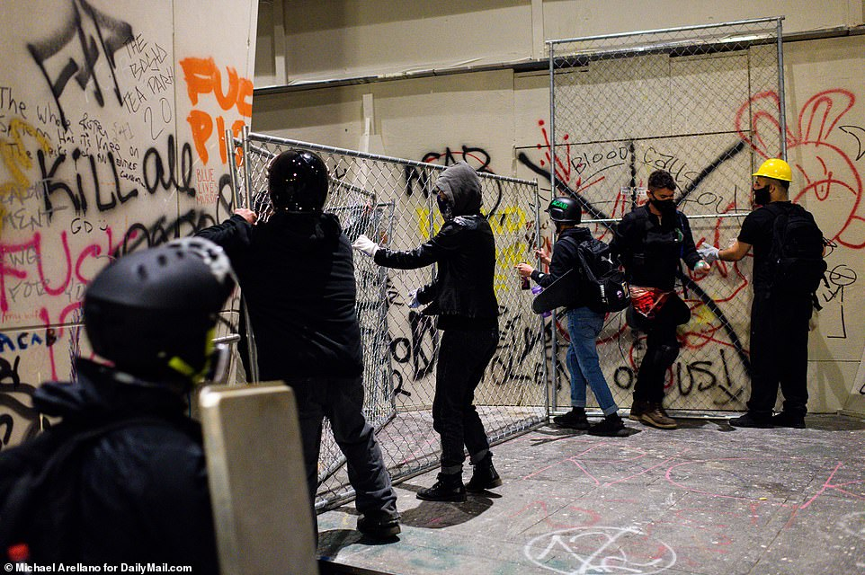 Protesters erect fencing in front of the Mark O. Hatfield federal courthouse entrance doors to block federal agents inside, but authorities eventually exited through the next door building and clashed with protesters