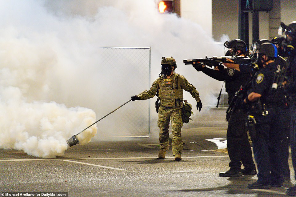 Several local Oregon politicians have blasted the arrival of federal agents (pictured center), who are not required to follow the same policing restrictions as local authorities and can use methods like tear gas