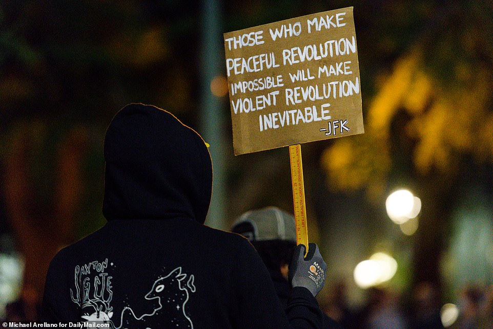 One person who joined tense protests in Portland on Friday night held a sign reading: 'Those who make peaceful revolution impossible will make violent revolution inevitable'