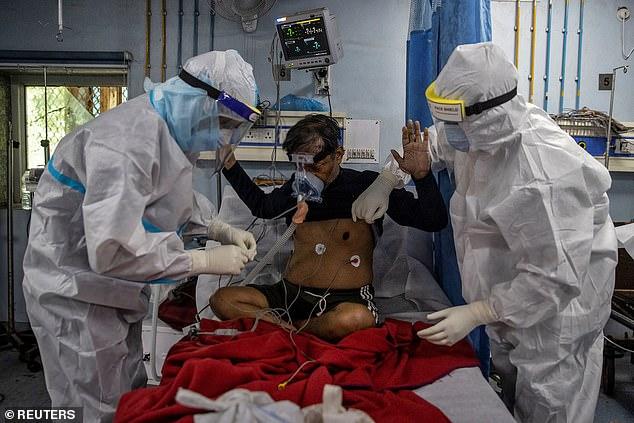 Medics tend to a coronavirus patient in the Intensive Care Unit at Lok Nayak Jai Prakash hospital in New Delhi, India