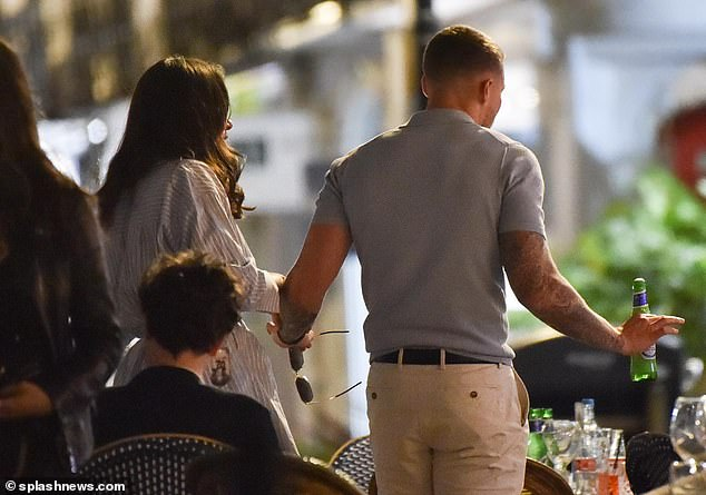 Affectionate: The pair appeared to return to their pals hand in hand after leaving the dinner table for a private chat