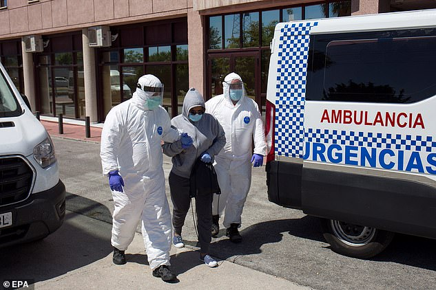 Health workers wearing protective suits take a woman to hospital after she tested positive for coronavirus at a Red Cross reception centre in Malaga which was the site of an outbreak