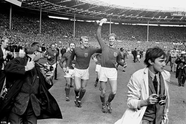 Jack Charlton holds the World Cup aloft as he parades it around Wembley with teammates Ray Wilson (left), George Cohen (second left) and Bobby Moore (second right) following their 4-2 win over West Germany on July 30, 1966